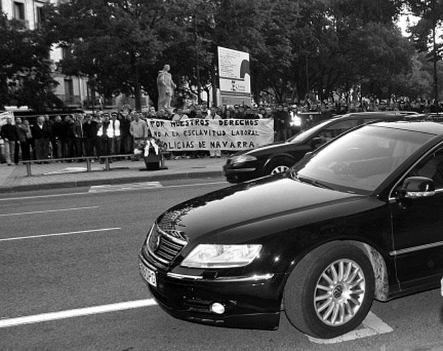Uno de los vehículos oficiales. Al fondo, una protesta policial