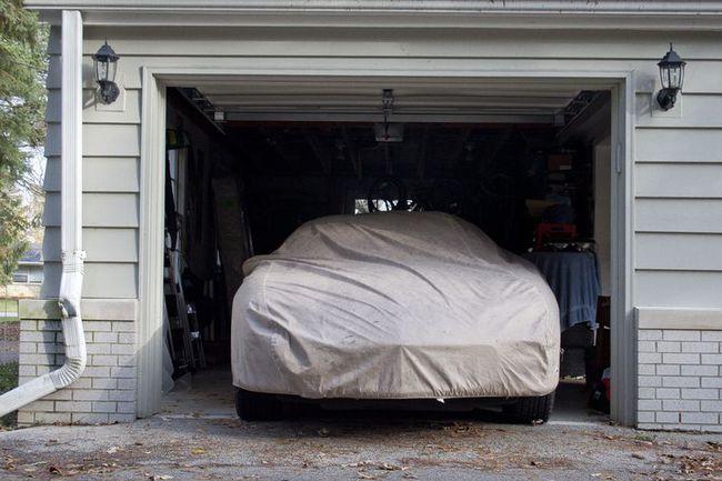 Coche en garaje con lona