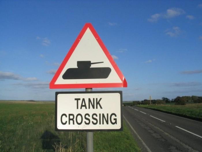 Señal tráfico peligro tanques cruzando
