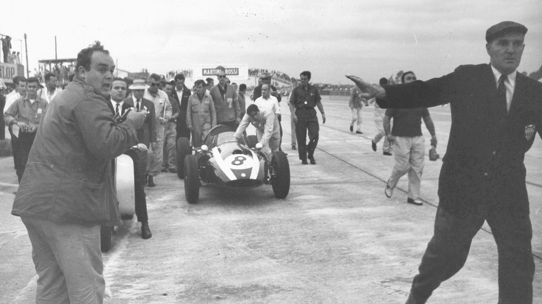Jack Brabham empuja su coche de carreras en el circuito en 1959