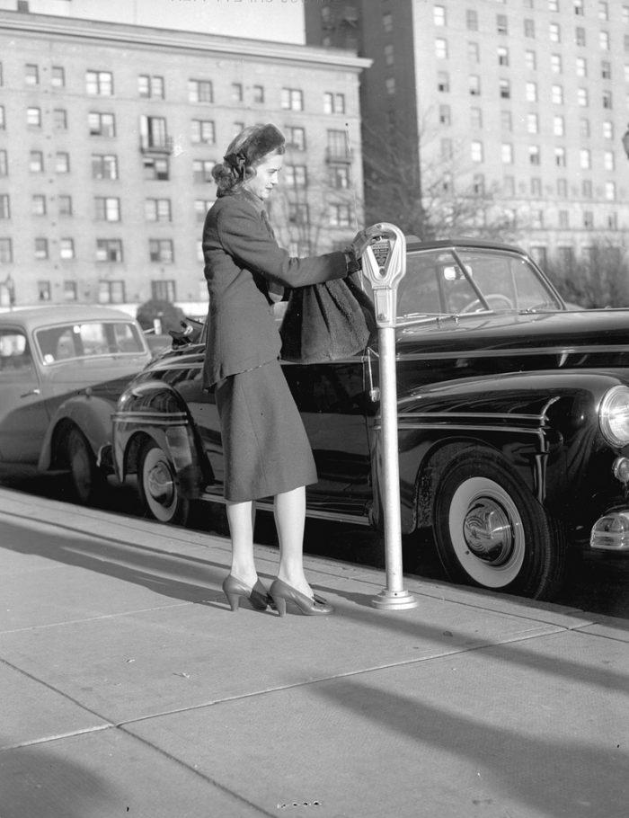 mujer pagando parquimetro