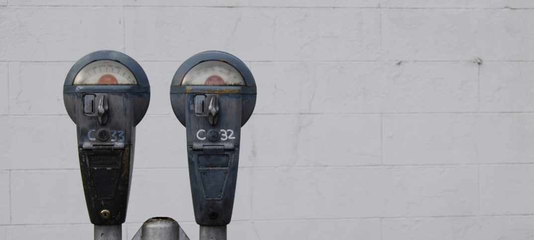 parkimetro en la calle sobre muro blanco
