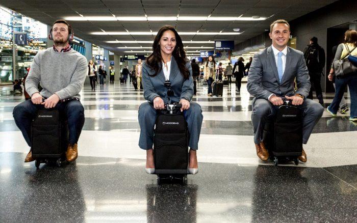 tres personas conducen maletas a motor