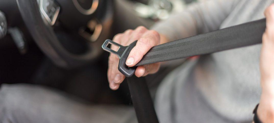Conductor poniendose el cinturon de seguridad